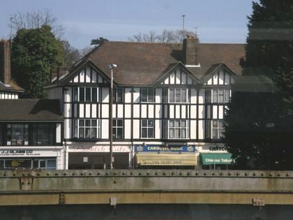View of a mock-Tudor building seen through a train window.