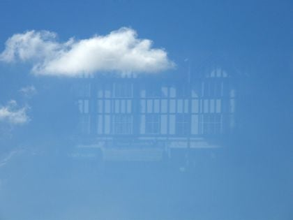 View of a blue sky - but a clear reflection of the mock-Tudor building opposite is also visible.